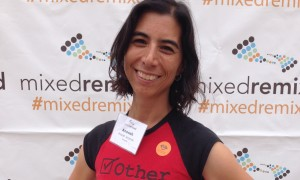A photo of Anoosh Jorjorian, a womxn with brown skin and dark hair, smiling, wearing a shirt that reads OTHER in front of a Mixed Remixed step and repeat.