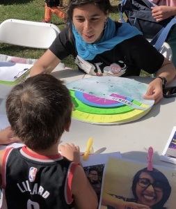 A woman with brown skin seated at a table with a wheel of gender terms, facing a child with his back to the camera.